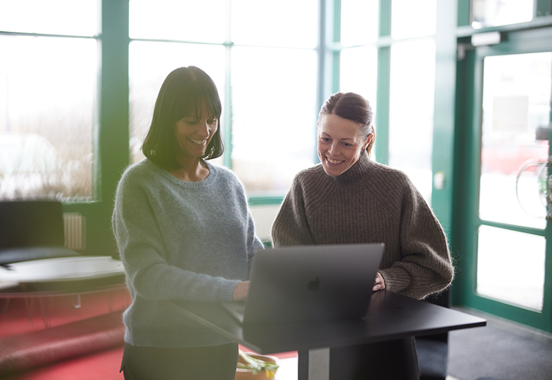 Två glada medarbetare tittar på en dator i kontorslandskap
