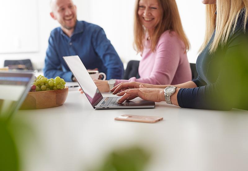 Tre medarbetare skrattar i kontorslokal med dator i fokus